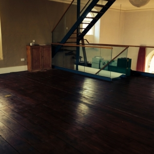 The floor prior to sanding. It has been stained with a dark stain, which we will remove in the sanding process.