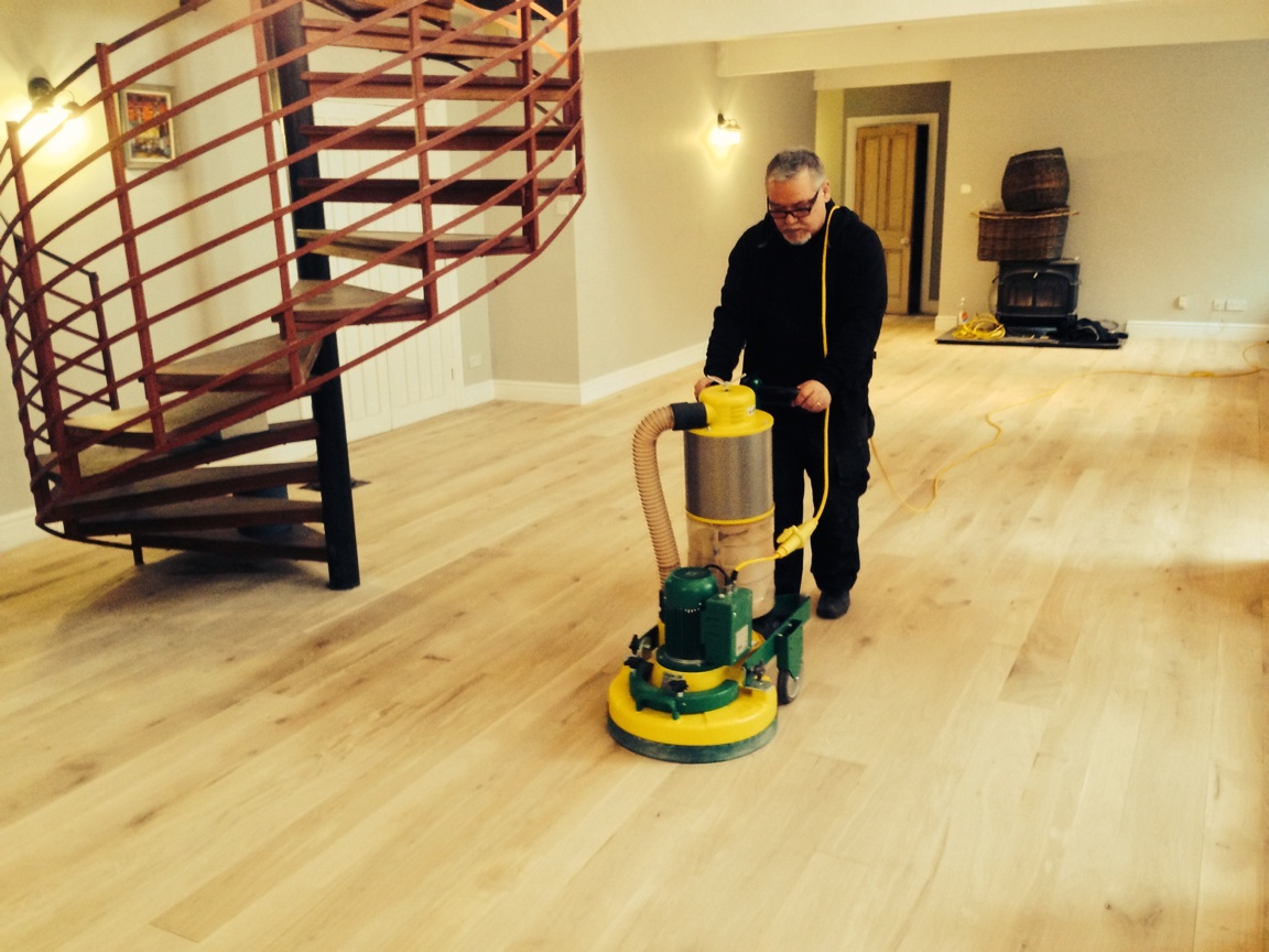 This photo shows Paul using the Laegler Trio to attain a flatter finish after he has sanded the floor with the Laegler belt sander